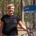 Laura Leivo sinisen frisbeegolfkorin vieressä.